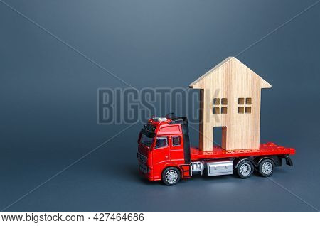 Red Truck Transports The Residence House. Delivery Services To Another House. A Moving Company. Tran