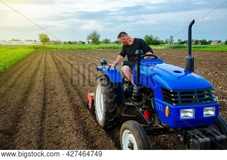 A Farmer Is Cultivating A Farm Field. Preparatory Earthworks Before Planting A New Crop. Land Cultiv