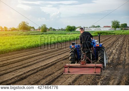 A Farm Tractor Works The Soil Of An Agricultural Field. Milling Soil, Crushing And Loosening Ground