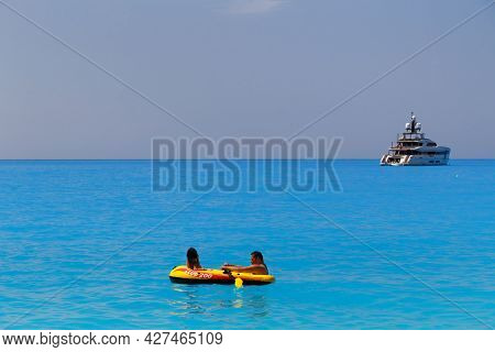 Myrtos Beach, Cephalonia Island, Greece - July, 13 2019: Father With Daughter Swimming In Inflatable