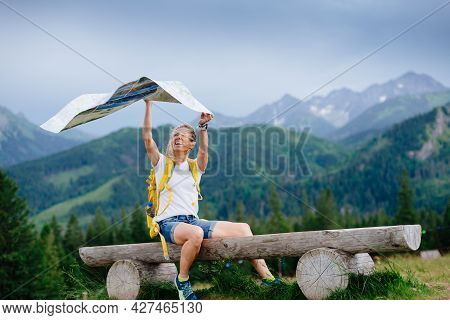 Woman Traveler With A Yellow Backpack Sits On A Bench With A Paper Map. The Wind Blows The Paper Map