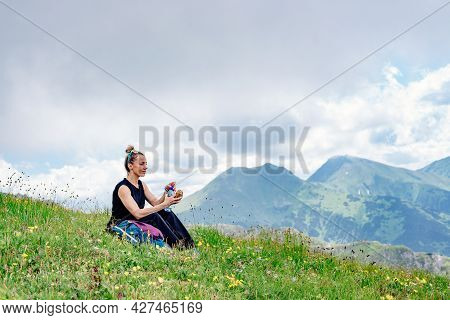 A Blonde Tourist Sits On The Grass, Eats And Drinks Water, Rests In The Beautiful Tatra Mountain.