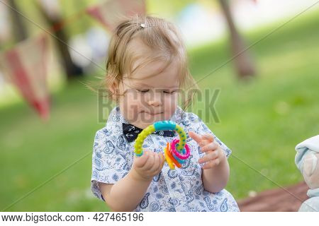 Dnepropetrovsk, Ukraine - 08.27.2017: Little Girl With Toys Rattles. Kid With A Toy.