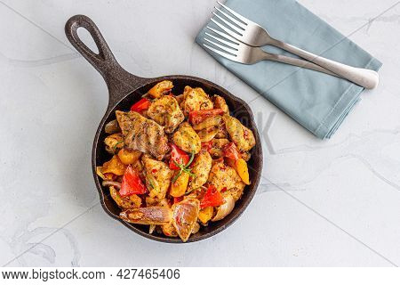 Baked Chicken And Veggies In A Cast Iron Skillet Top Down Photo On White Background
