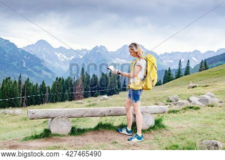 Adventurous Woman Navigating With A Topographic Map In Beautiful Mountains.