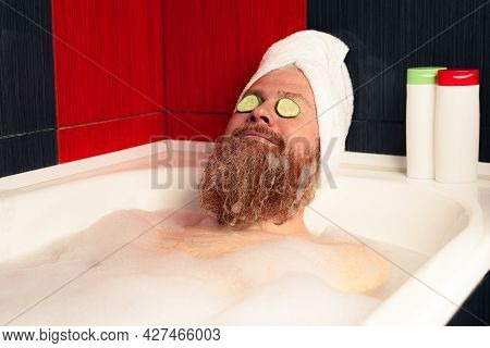 Cute Bearded Man Taking Bath With Head Wrapped In Towel And Cucumber Slices On His Eyes. Funny Hipst
