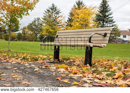 Autumn In The Park. Fallen Leaves Near Bench And Road In A Local Park With Houses And Trees In The B