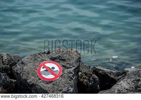 No Swimming Sign On Rock Beside Water. Warning.