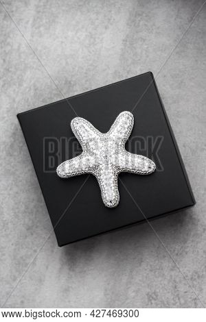 Seed Bead Embroidered Brooch In A Shape Of Starfish On Black Box On Concrete Background