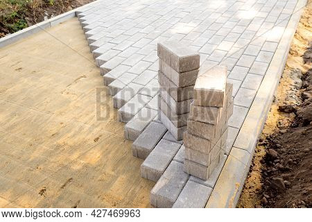 Top View Of The Edge Of Surface With Laid Gray Paving Slabs. Surface With Sandy Mixture Is Visible.