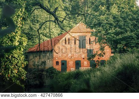 An Old Idyllic Farmhouse In Summer On A Small River