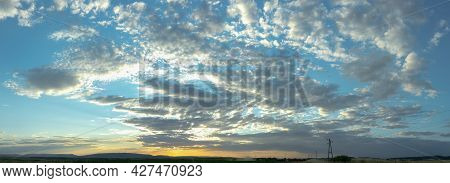 Panorama View On A Moody Yellow Sunset Between The Clouds Sky