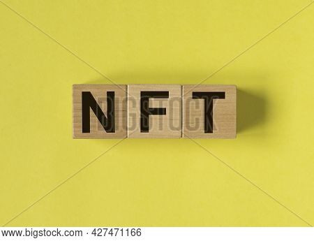 Nft Acronym On Wooden Dices On Yellow Background.