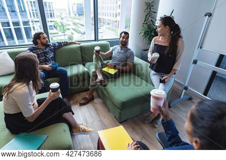 Diverse group of creative colleagues holding takeaway coffees, talking at casual meeting. modern office of a creative design business.