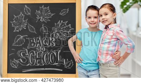 education, learning and people concept - happy smiling little girls hugging over chalkboard with back to school lettering on background