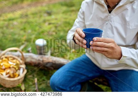 picking season and leisure people concept - close up of man with wicker basket of mushrooms sitting on fallen tree and drinking tea in autumn forest