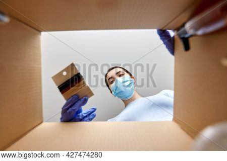 home delivery, shipping and pandemic concept - woman in protective medical mask and gloves unpacking parcel box with elastic hair bands and beauty products