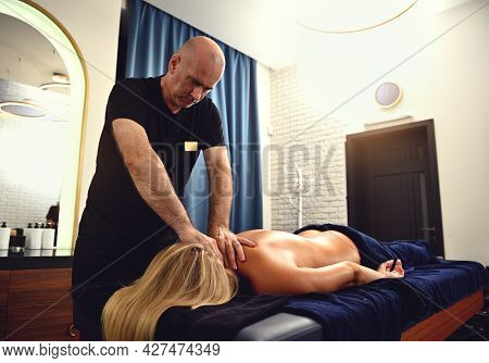 Young Woman Being Massaged By Physiotherapist On Massage Table In Clinic. Professional Neck Massage