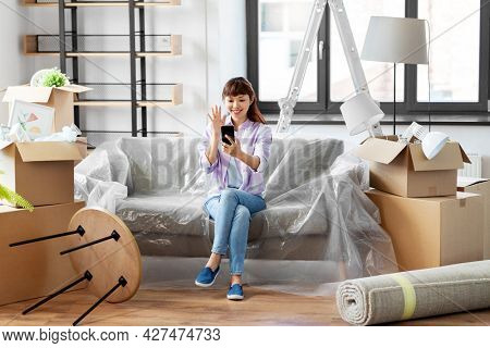 moving, people and real estate concept - happy smiling asian woman with smartphone and boxes having video call at new home