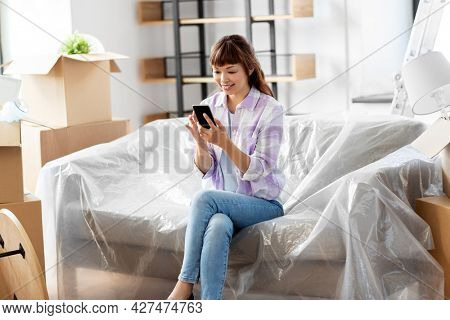 moving, people and real estate concept - happy smiling asian woman with smartphone and boxes at new home