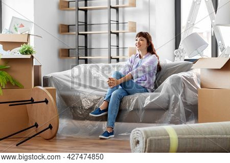 people, repair and real estate concept - happy smiling asian woman with stuff moving to new home