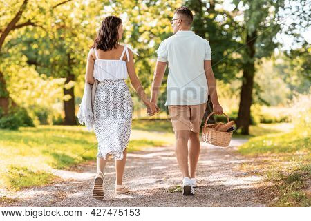 leisure, vacation and people concept - happy couple with picnic basket and blanket walking at summer park