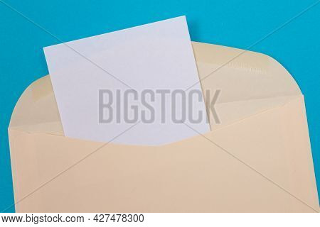 Beige Envelope With Blank White Sheet Of Paper Inside, Lying On Blue Background - Mock Up With Copy