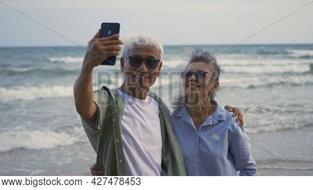 Happy Asian Senior Man And Woman Couple Smile Taking Selfie Photo With Smartphone On The Beach, Roma