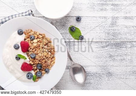 Yogurt With Baked Granola And Berries In White Ceramic Plate On Wooden Background. Healthy Breakfast