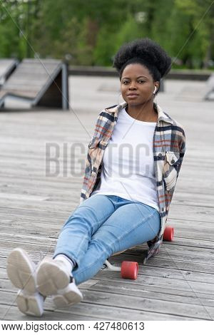 Relaxed Casual African Girl Chilling After Skateboarding In Skatepark Sit On Longboard Listen Music