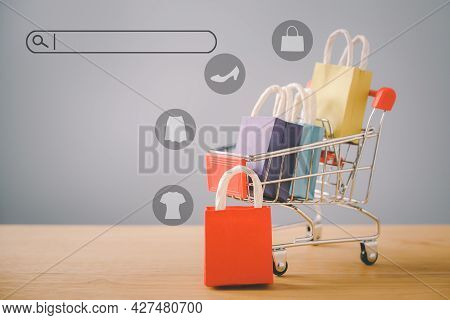 Small Red Shopping Paper Bag On Wood And Blurred  Cart, Search Bar Beside With Copy Space, Online Sh
