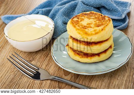 Blue Napkin, Bowl With Condensed Milk, Stack Of Cottage Cheese Pancakes In Turquoise Saucer, Fork On