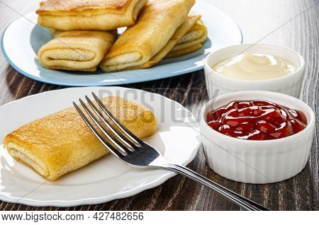 Few Fried Pancake Rolls In Light-blue Plate On Background, Fork In White Plate With Pancake In White