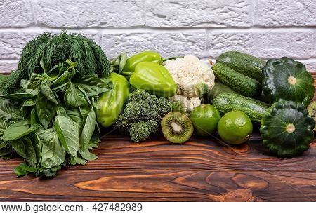 Colorful Summer Vegetable Frame. Variety Of Raw Green Vegetables As Frame Over Dark Wooden Texture B