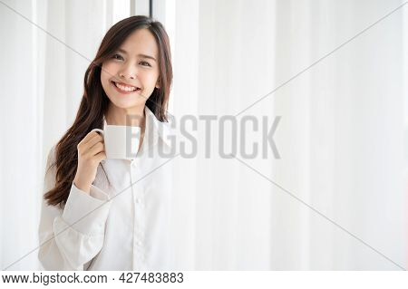 Young Asian Beautiful Woman Clothing White Pyjamas And Drink Coffee Beside Window At Morning In Bedr