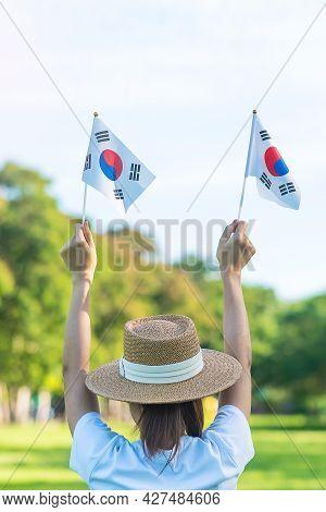 Woman Hand Holding Korea Flag On Nature Background. National Foundation, Gaecheonjeol, Public Nation