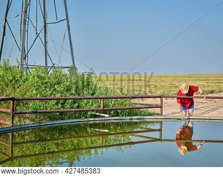 older farmer or rancher at a cattle water tank with water coming from windmill pump in a prairie - Pawnee National Grassland in northern Colorado