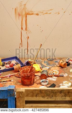 Abstract Smears Of Brown Paint On Beige Wall Near Messy Wooden Table With Dirty Jars Brushes And Toy