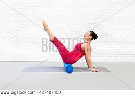 Teaser Exercise With Foam Roller. Attractive Adult Caucasian Woman In Red Sportswear Does Pilates Ro