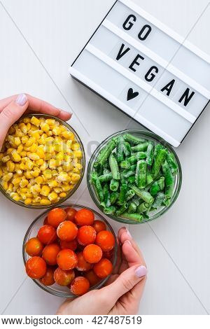 Lightbox With Text Go Vegan Three Bowls Of Frozen Vegetables Food Of Yellow Corn, Green Beans, Red T