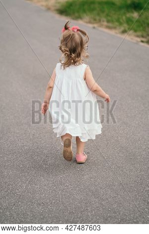 A Child In A White Dress Runs Down The Path. Little Kid With His Back To The Photographer. Happy Chi