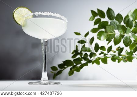 Margarita Cocktail In Glass Goblet With Sugar Rim And Slice Of Lime In Summer Sunlight With Green Br