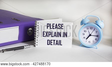 A Sign With The Inscription Please Explain In Detail On The Table With Document Folder, Alarm Clock