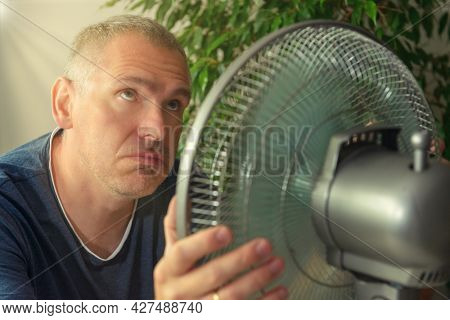 Man suffers from heat while sitting in the oom and tries to cool off by the fan