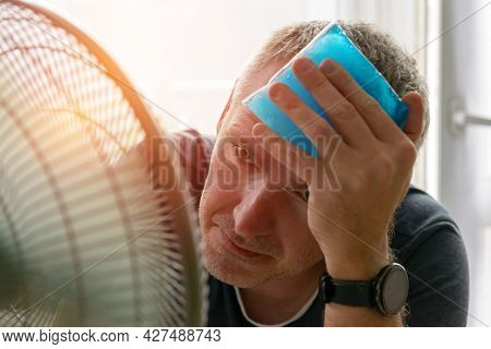 Man suffers from heat and headache while sitting in the room and tries to cool off by the fan