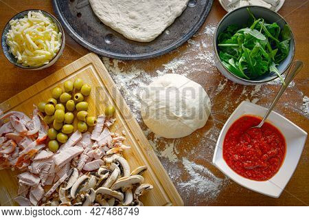 Preparing the Italian pizza known as the Margherita. Yeast dough pizza with mushrooms, mozzarella cheese and tomato sauce.