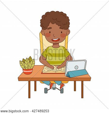 Little African American Boy At Table In Front Of Tablet Pc Training And Doing Homework As Home Study