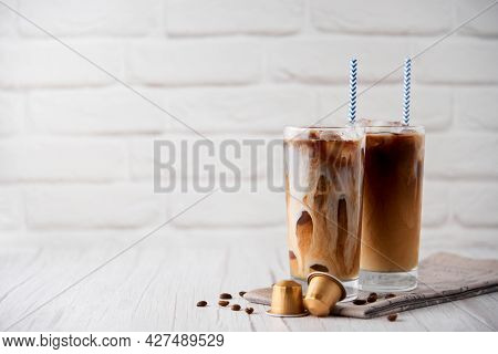 Iced Coffee Latte Cappuccino In A Tall Glass With Cream Or Milk Andbeans, Gold Capsules Straws On A