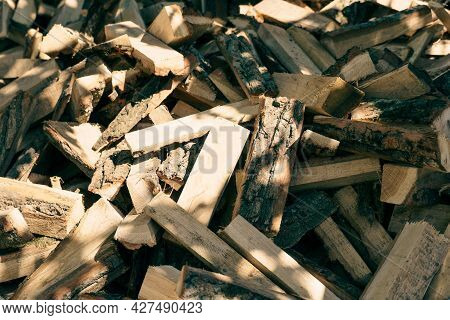 The Background Of The Firewood Is Chopped Firewood On A Stack. Dry Logs Of Firewood In A Heap.