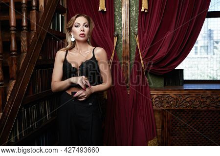 Wealthy middle-aged woman with evening makeup and hairstyle stands in black dress in a luxury apartment. Luxury lifestyle.